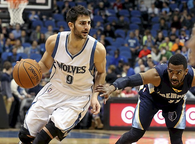 Minnesota Timberwolves' Ricky Rubio, left, of Spain, drives as Memphis Grizzlies' Mike Conley pushes him in the first quarter of an NBA basketball game, Friday, Feb. 6, 2015, in Minneapolis. (AP Photo/Jim Mone)